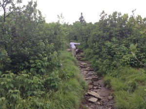 My daughter on a slippery, rocky path on a a day so overcast there was not much of a view.